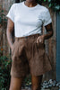 Close up of woman wearing brown suede shorts.