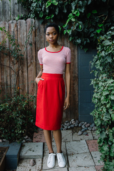 Woman wearing apple red pencil skirt.