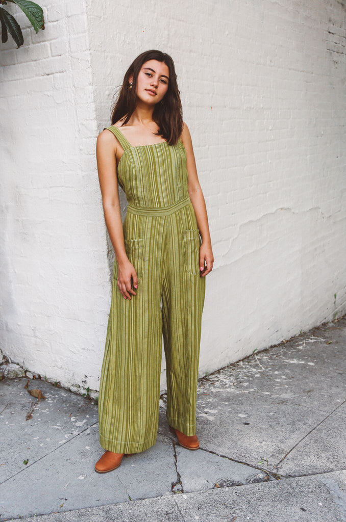 Woman wearing moss green striped linen jumpsuit.