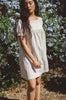 Woman wearing cream linen short sleeve peasant dress outside