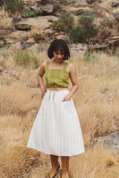 Woman wearing green linen top and cream skirt