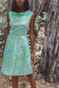 Woman wearing green and blue paisley pleated dress