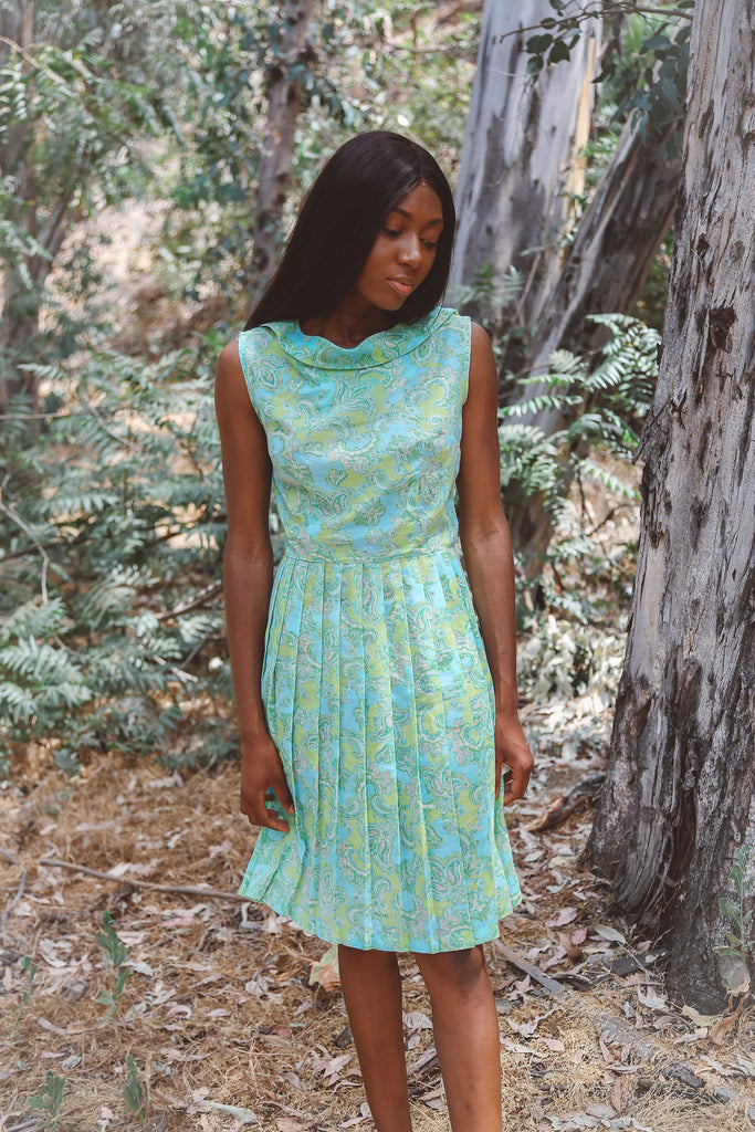 Woma wearing green and blue paisley pleated dress