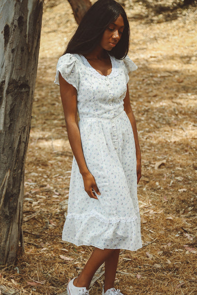 Woman wearing white floral gunne sax dress