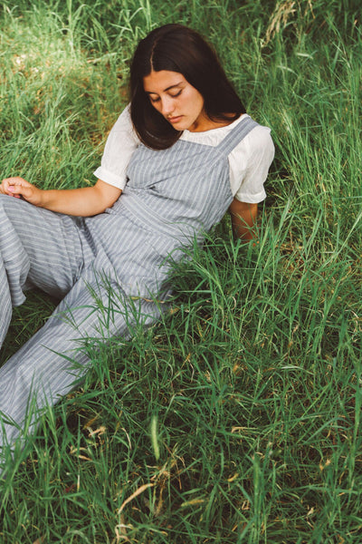 Woman lying in grass wearing striped overalls and peasant blouse.