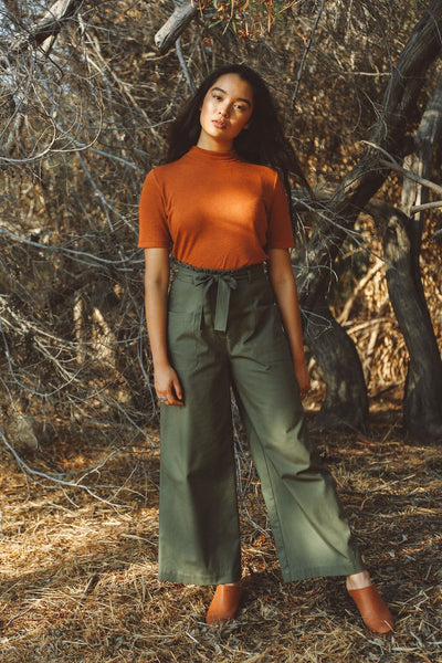 Woman wearing rust mockneck sweater tee with pants