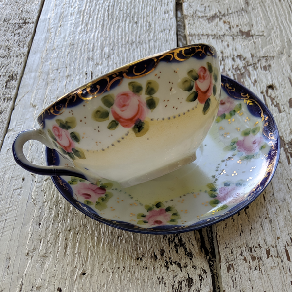 Hand painted rose tea cup and saucer set gold embellishment navy blue edge