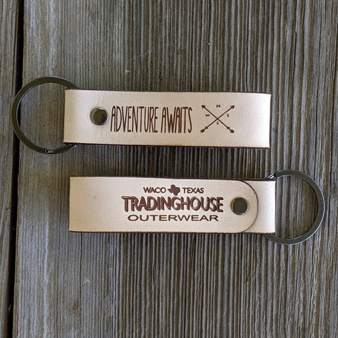 get outdoors tradinghouse outerwear logo adventure awaits compass leather keychain