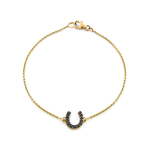 Image of a black diamond & gold horseshoe bracelet.