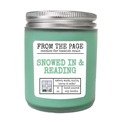 "Light green candle with label ""Snowed in and Reading"""