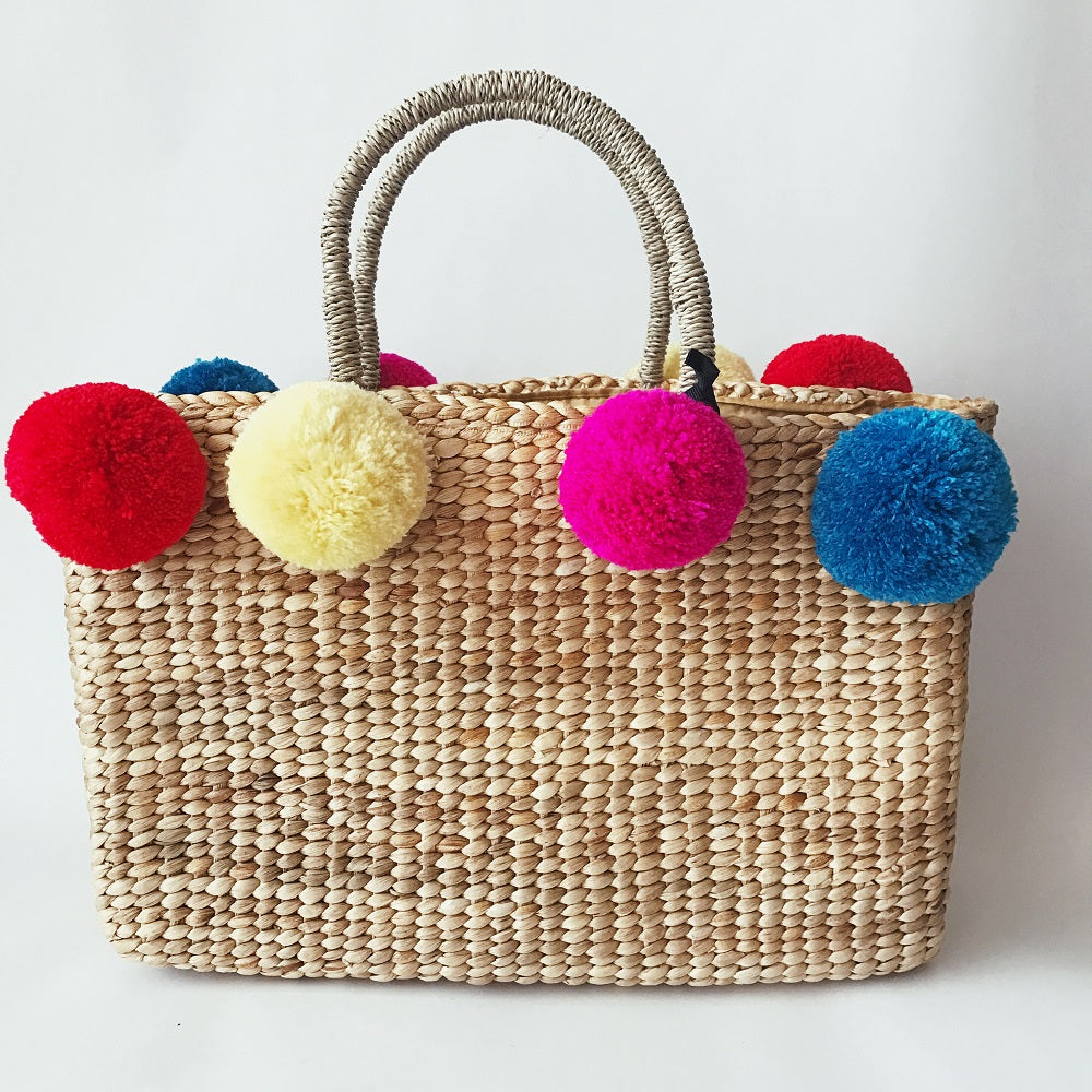 Strawbag with colorful pom poms fair trade