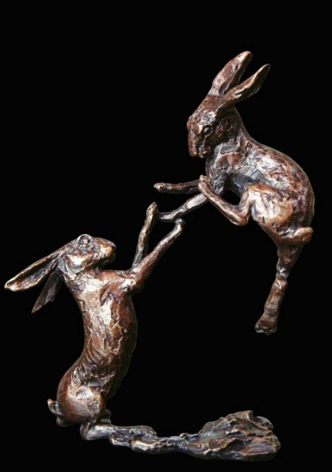 a bronze miniature sculpture of two boxing hares