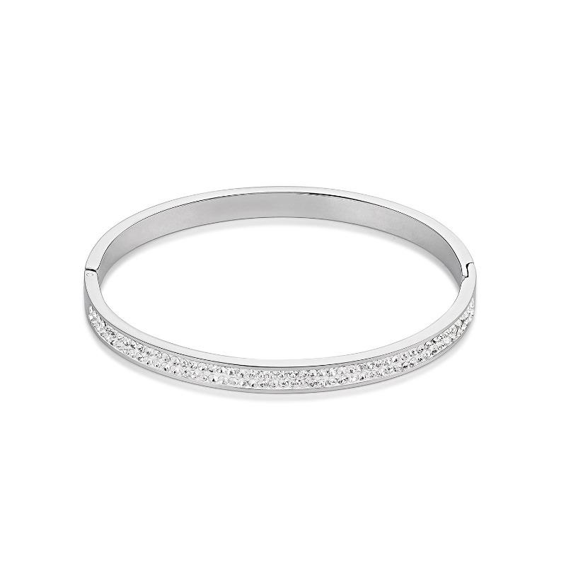 Stainless steel hinged oval bangle set with two rows of crystals along the front
