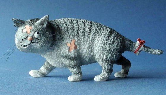 A comical cat figurine of a cat who has come off worse in a fight
