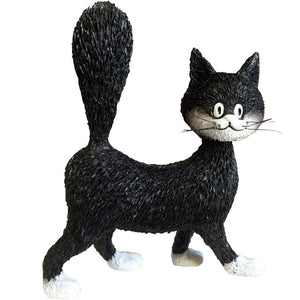 A black and white cat figurine looking bushy tailed and grown up