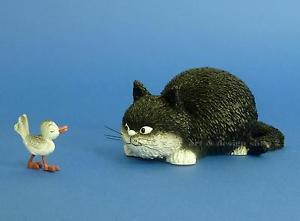A black and white cat figurine as he stalks a small bird