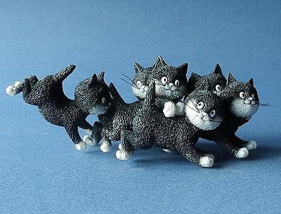 A figurine of a group of kittens playing and chasing