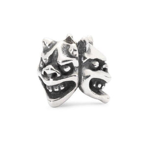 A silver charm bead featuring three faces, representing Intensity, friendship and joy.
