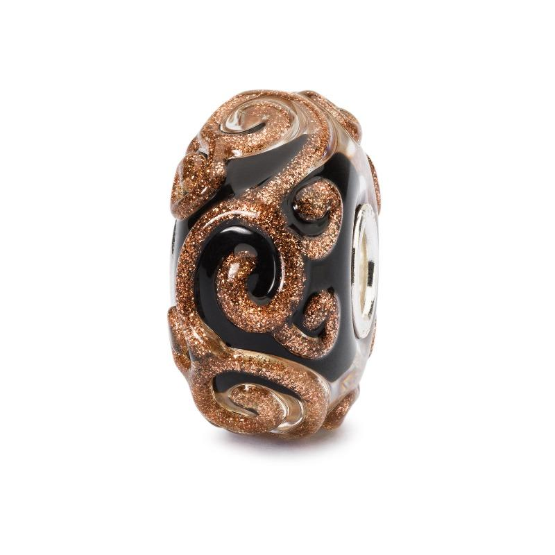 A black back bead which has raised swirls of glittering gold for modern charm bracelets