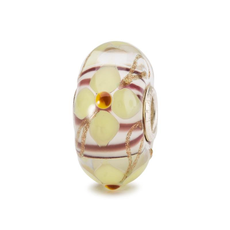 Soft yellow flower and swirls of copper abound on this glass bead from Trollbeads