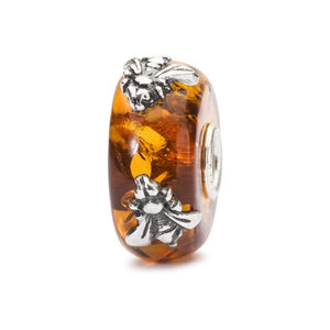 Trollbeads amber charm bead with two silver flies on the surface of the bead