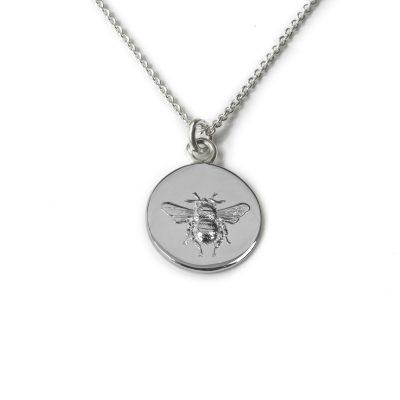 Silver pendant of a bee embossed on a silver disc, hanging on a silver chain.