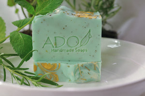 Sea Green Claity Soap on a White Plate Accented with Herbs and Rosemary and Spearming Plants in the Background