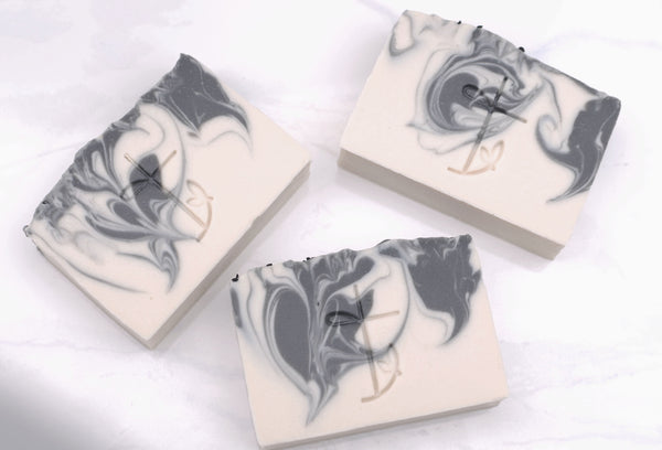 Three  bats of Lions Den Soap Lying Flat on a Neutral Background