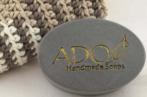 logo prominant image of charcoal soap laying on a crochet washcloth