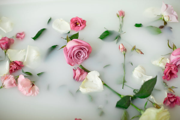 tub filled with artisan milk bath and floating long stem flowers