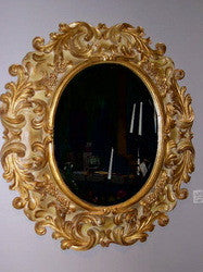 "Reproduction hand-carved and gilt oval ""Medici"" mirror with beveled glass"
