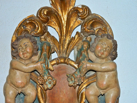 Antique carved, polychromed and gilt cherubs with shield
