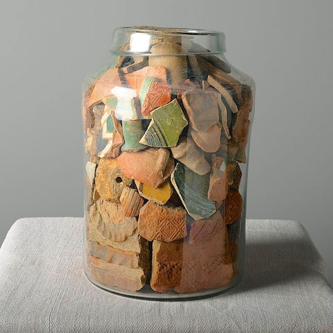 "Glass jar filled with antique ""Fajalauza"" majolica fragments"