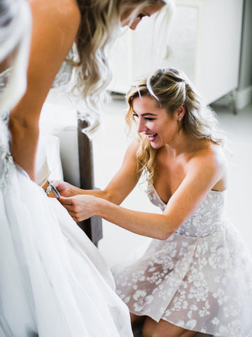 Hayley Paige Lauren Burnham putting on wedding garter
