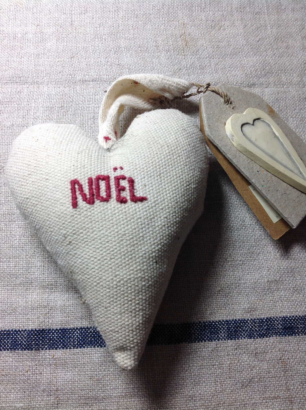 Cream hanging Christmas decoration heart with Noel embroidered on the front.