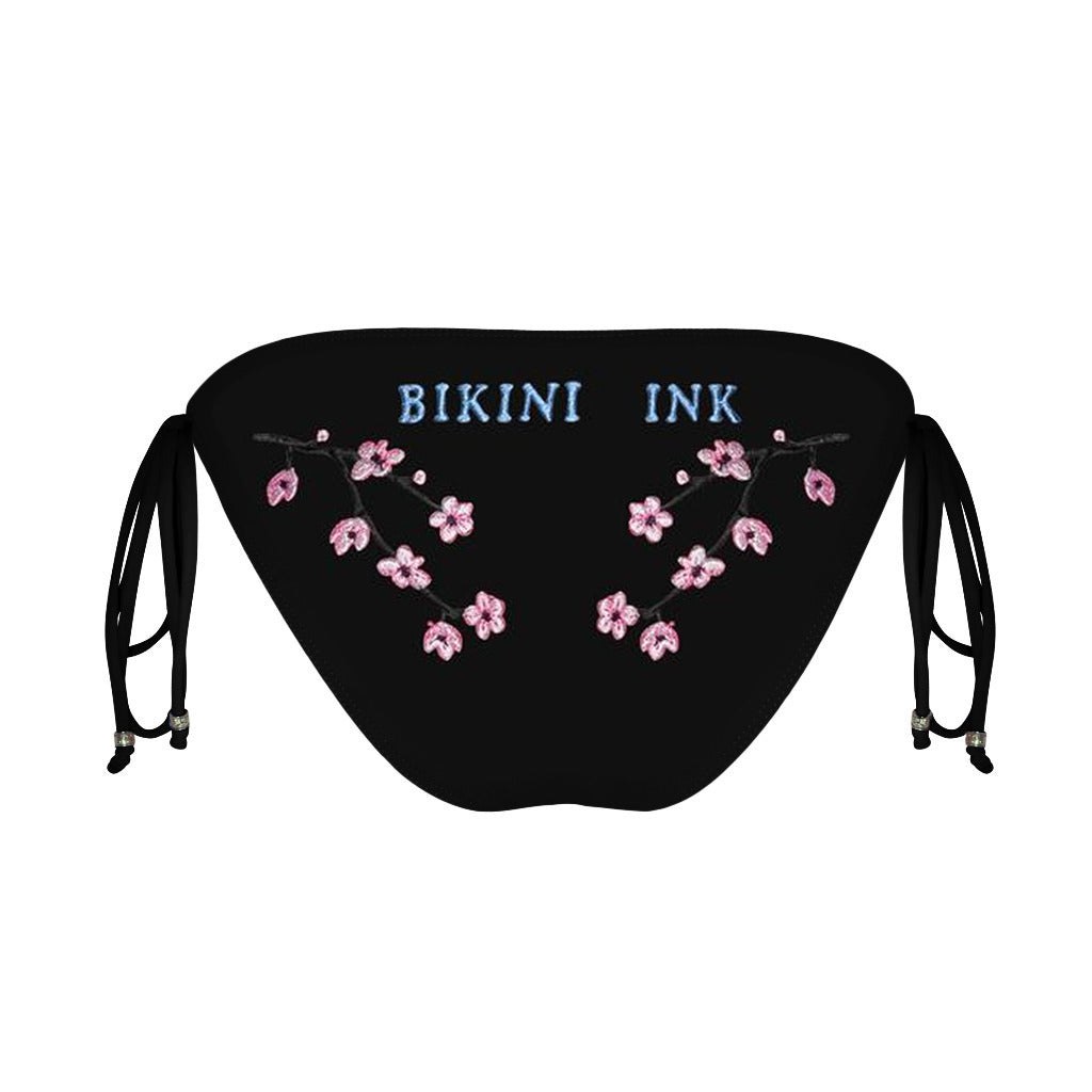 Bikini Ink embroidered cherry blossom bikini in demand inked bikini in black tie side cut. Stylish black  Bikini Ink bikini bottom with cherry blossom tattoo inspired  bikini artwork
