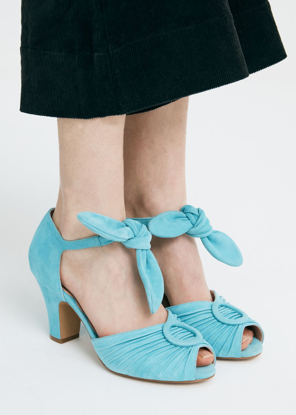 Loretta in soft turquoise blue suede by Miss L Fire is a vintage inspired peep toe sandal with 8cm heel and soft ankle tie straps. Vamp features delicate pleating and covered buckle detail.