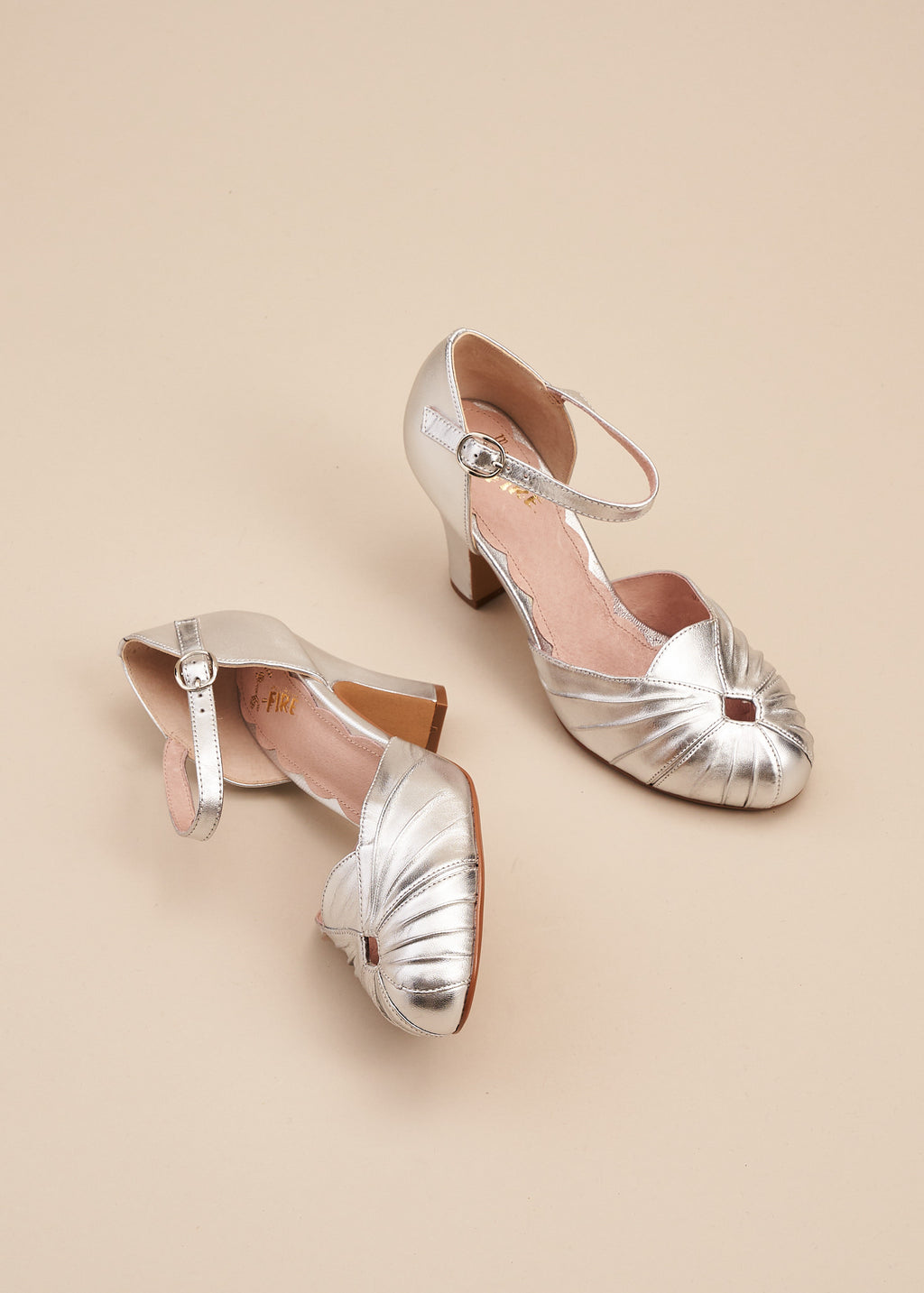 Amber in shiny silver metallic leather is a two part bar shoe with adjustable strap and 8 cm heel, bu Miss L Fire.  Vintage inspired, with delicate ruching on the toe. Perfect Bridal style.