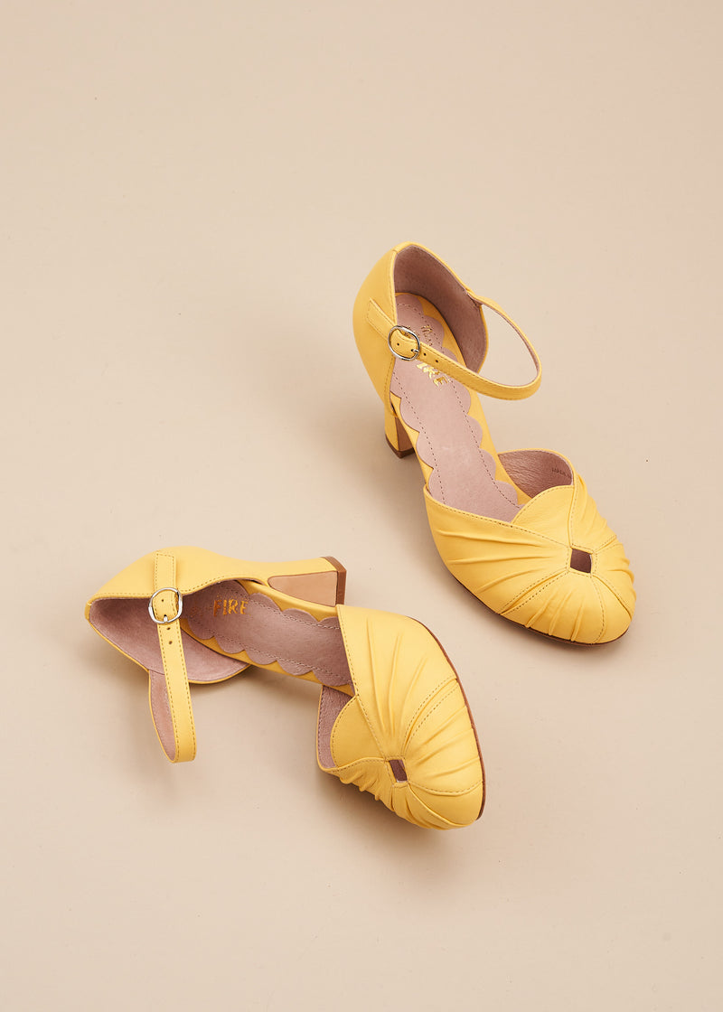 Amber in butter soft lemon yellow leather is a two part, vintage inspired bar shoe by designer Miss L Fire. Amber features an 8cm heel, ruched detail on the toe and an adjustable strap.