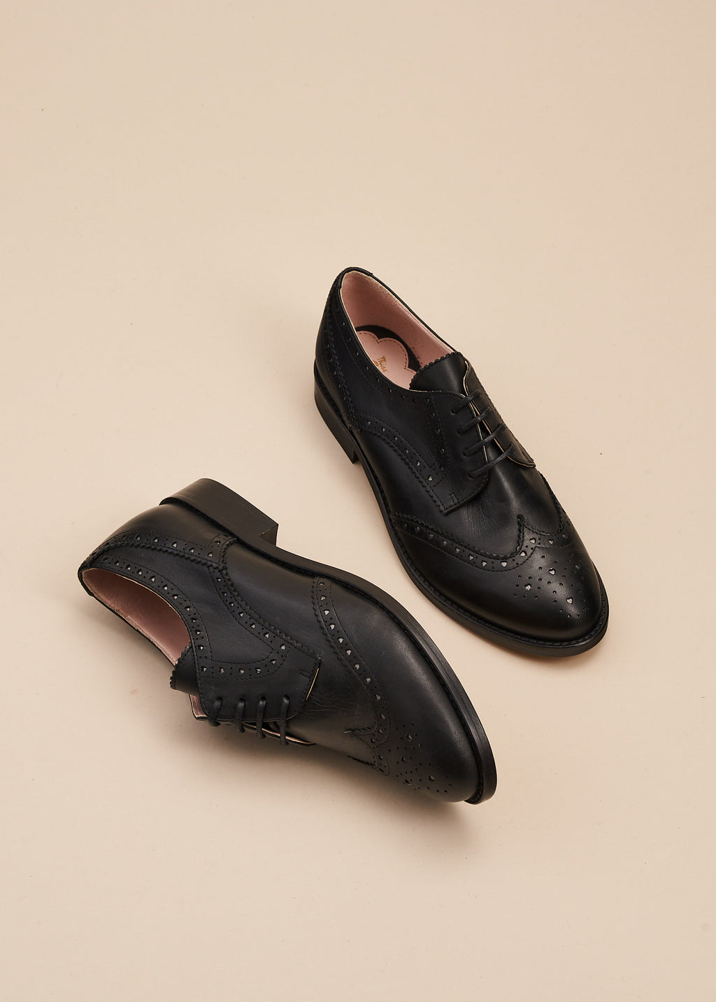 Audrey in black leather is the perfect at home, or at work lace up vintage inspired brogue shoe  with 2.5cm heel. Audrey features tiny heart-shaped cut outs which add a feminine touch to a traditionally masculine style .  By Miss L Fire.