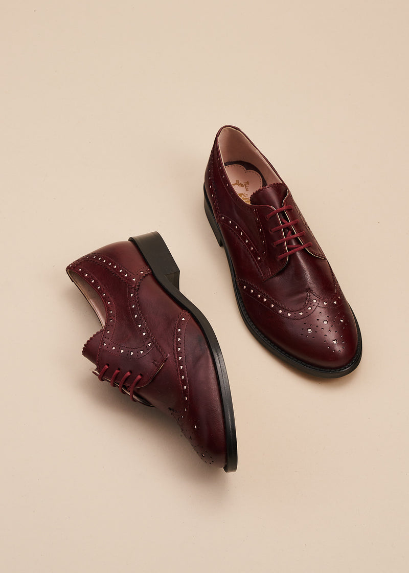 Audrey in red wine leather is the perfect at home, or at work lace up vintage inspired brogue shoe  with 2.5cm heel. Audrey features tiny heart-shaped cut outs which add a feminine touch to a traditionally masculine style .  By Miss L Fire.