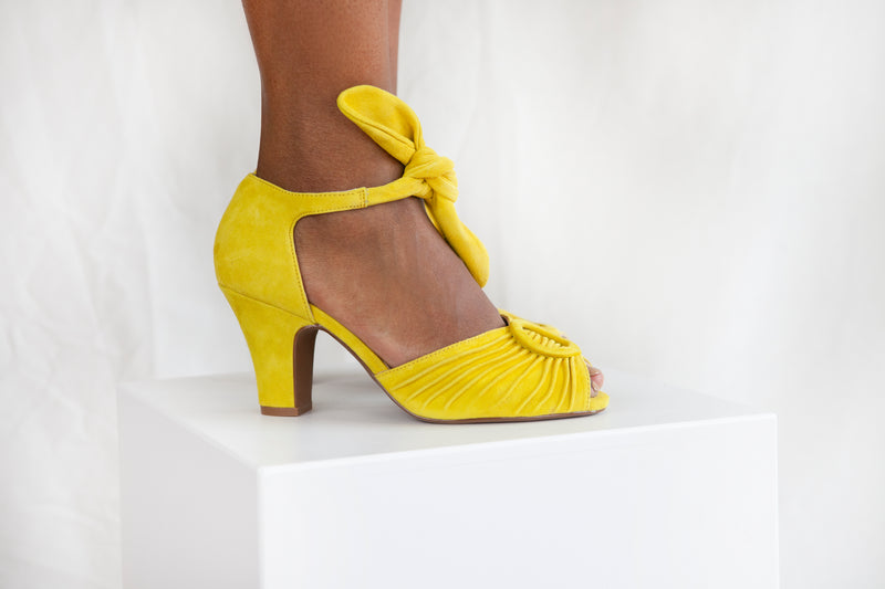 Loretta sunflower yellow peep toe suede sandal with ruched detail and tie straps. Vintage inspired, always ethically produced.
