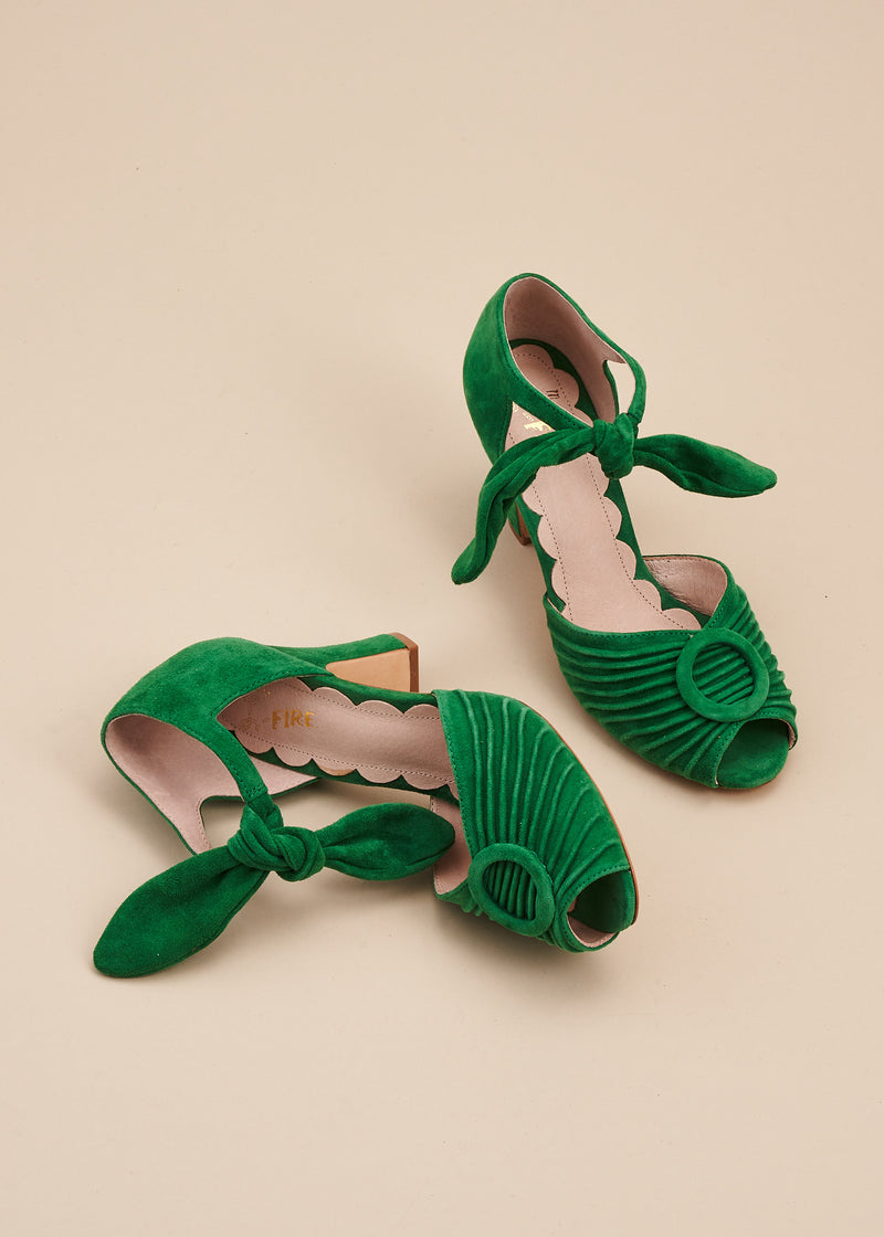 Loretta in soft Kelly green suede by Miss L Fire is a vintage inspired peep toe sandal with 8cm heel and soft ankle tie straps. Vamp features delicate pleating and covered buckle detail.