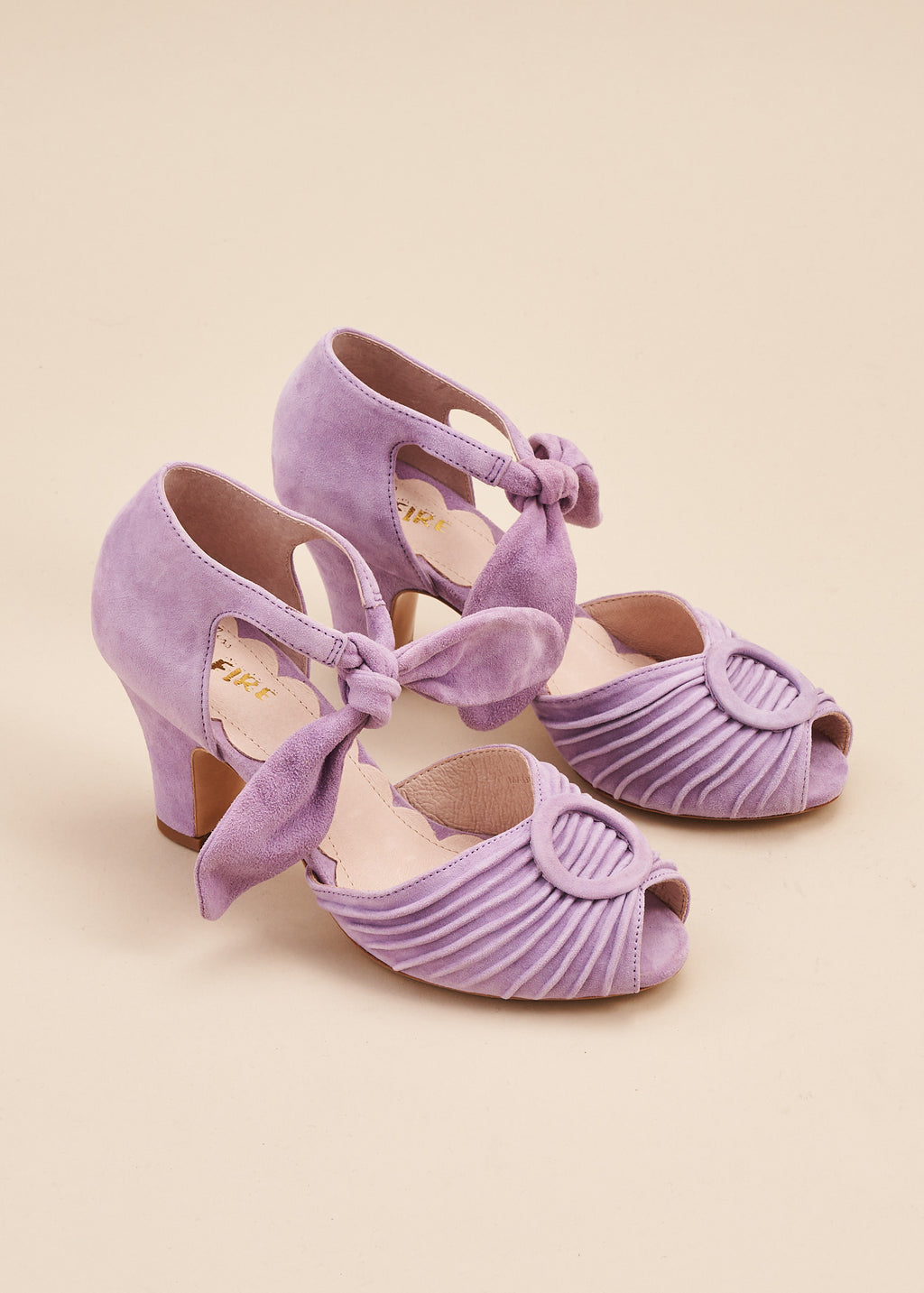 Loretta in soft pastel lilac suede by Miss L Fire is a vintage inspired peep toe sandal with 8cm heel and soft ankle tie straps. Vamp features delicate pleating and covered buckle detail. Perfect Bridal shoe.