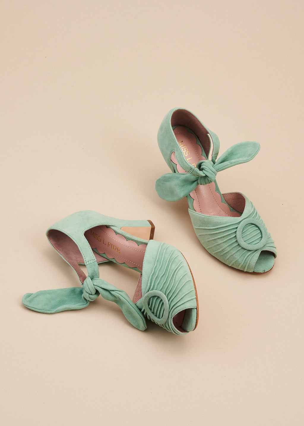 Loretta in soft mint green suede by Miss L Fire is a vintage inspired peep toe sandal with 8cm heel and soft ankle tie straps. Vamp features delicate pleating and covered buckle detail.