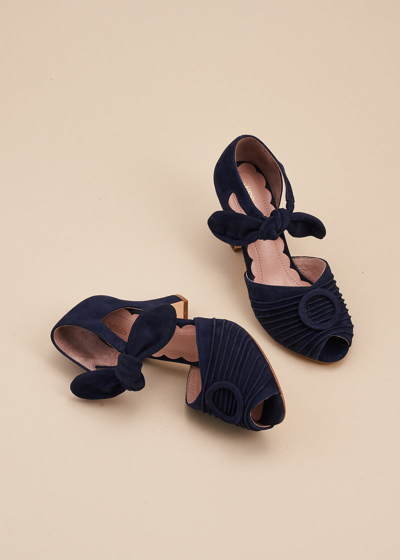 Loretta in soft deep navy blue suede by Miss L Fire is a vintage inspired peep toe sandal with 8cm heel and soft ankle tie straps. Vamp features delicate pleating and covered buckle detail.
