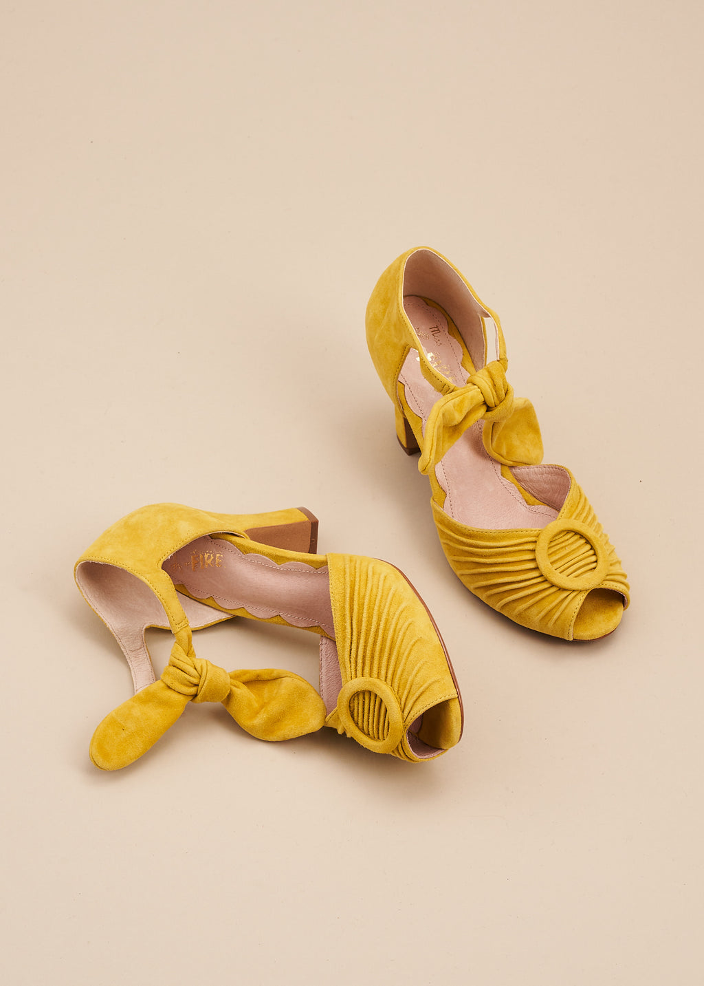 Loretta in sunny yellow suede by Miss L Fire is a vintage inspired peep toe sandal with 8cm heel and soft ankle tie straps. Vamp features delicate pleating and covered buckle detail.