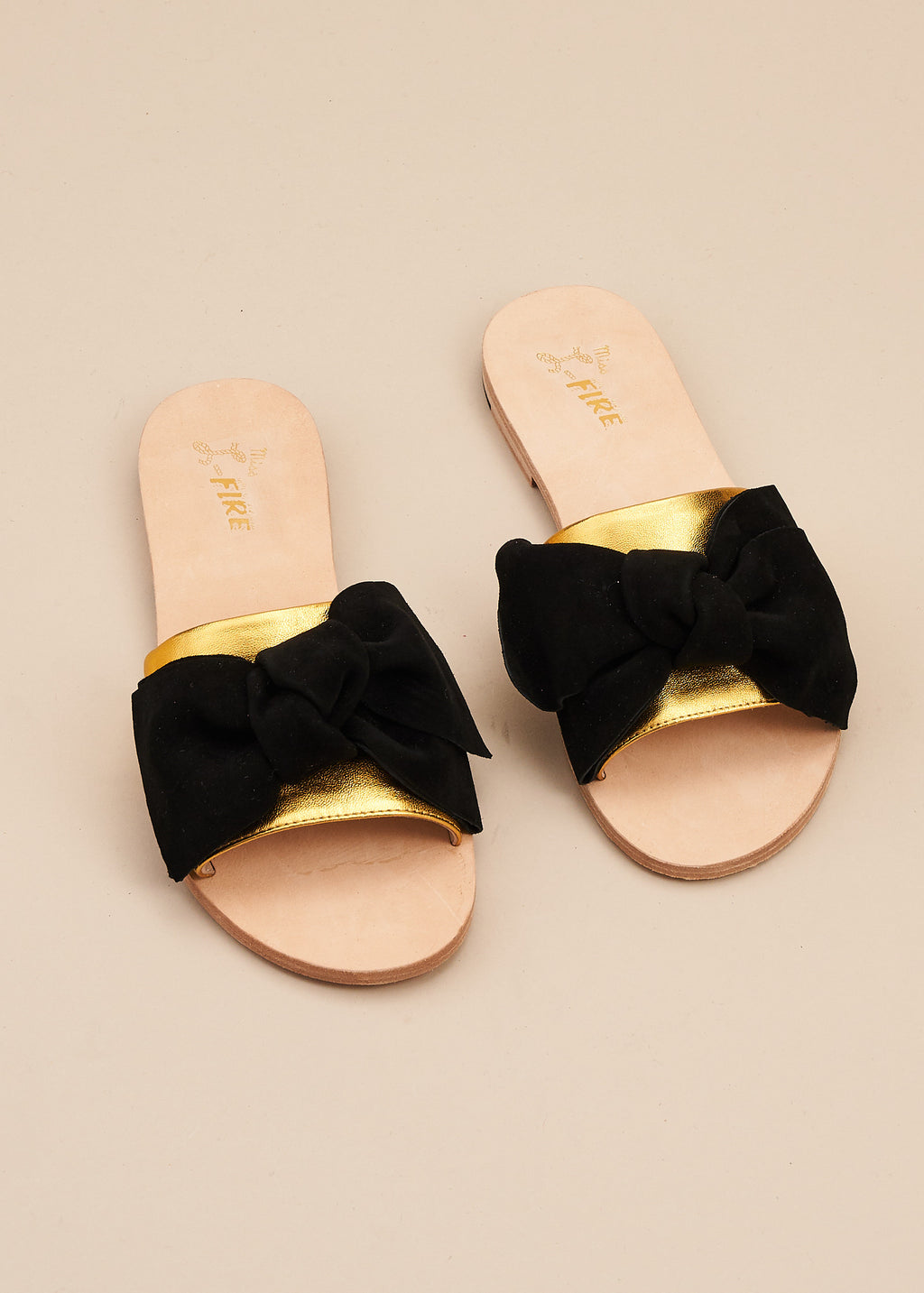 Serafina is a super cute slide with gold leather band and soft black suede bow. It is the perfect stay-at-home slide. All leather upper, insole and outsole, this is a little indoor luxury at an affordable price. By Miss L Fire.