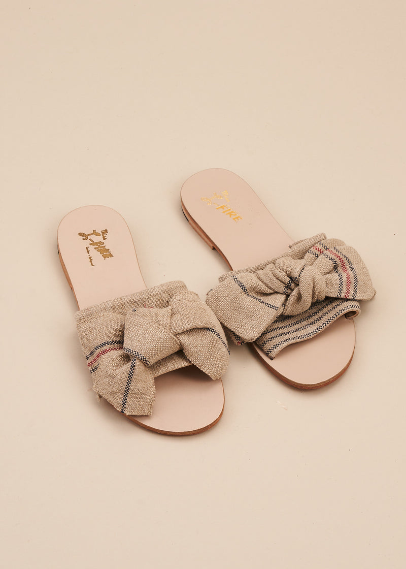 Serafina is a super cute slide with natural striped linen band and soft hand-tied bow trim. It is the perfect stay-at-home slide. All leather upper, insole and outsole, this is a little indoor luxury at an affordable price. By Miss L Fire.
