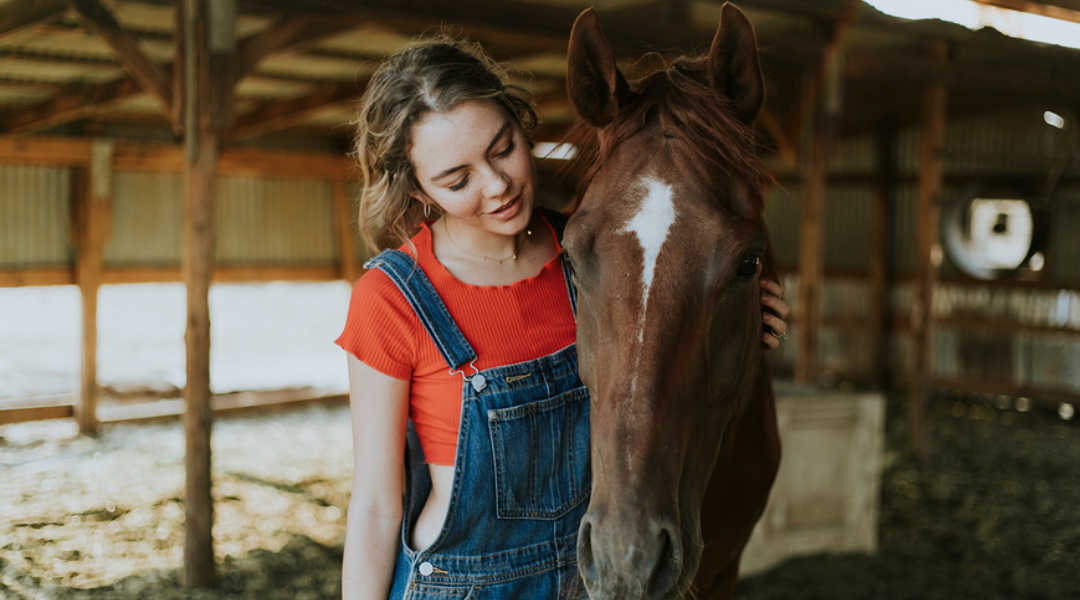 horse and young woman in barn